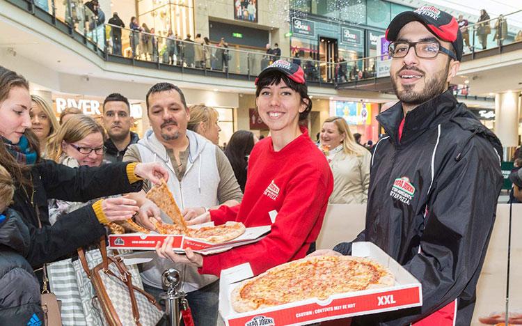 Experiential promo staff serve pizza